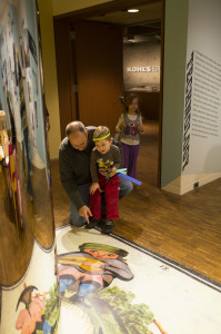 Families check out the anamorph in Illusions: Near and Far. Photo by Front Room Photography